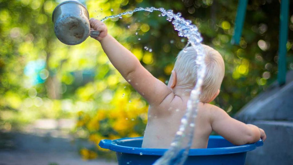 baby playing in water bucket